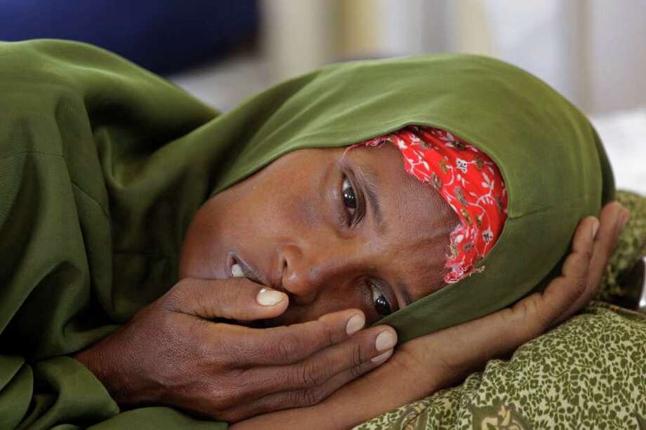 "In this Tuesday, July 26, 2011 photo, a  malnourished woman lies in a field hospital of the International Rescue Committee, IRC, in the town of  Dadaab, Kenya,. The U.N. will airlift emergency rations this week to parts of drought-ravaged Somalia that militants banned it from more than two years ago, in a crisis intervention to keep hungry refugees from dying along what an official calls the ""roads of death."" Tens of thousands already have trekked to neighboring Kenya and Ethiopia, hoping to get aid in refugee camps. (AP Photo/Schalk van Zuydam) Photo: Schalk Van Zuydam, STF / Copyright 2011 The Associated Press. All rights reserved. This material may not be published, broadcast, rewritten or redistribu"