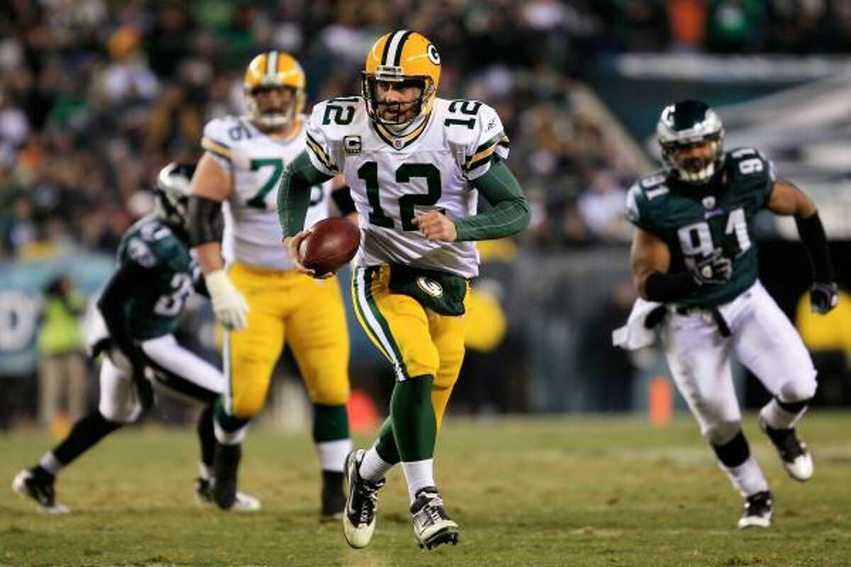 Packers quarterback Aaron Rodgers carries the ball and picks up a first down.