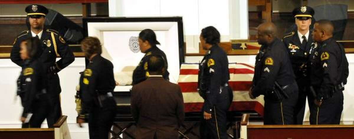 Members of the Dallas Police Department file past the casket at the funeral of Arlington police Officer Jillian Michelle Smith at Mount Olive Baptist Church in Arlington, Texas. Smith was killed last week while answering a domestic disturbance call.
