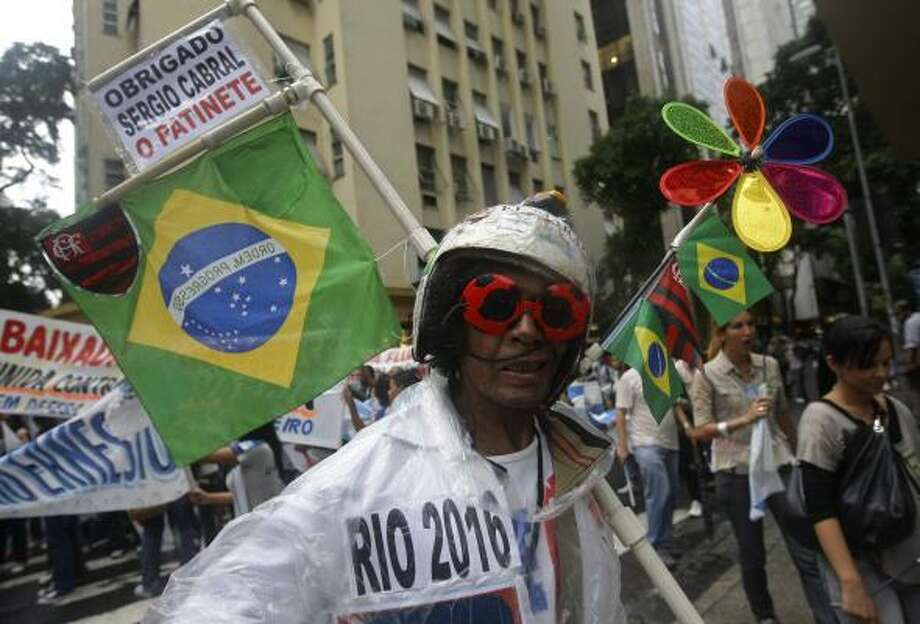 Costumed and carrying a sign, a carioca — as the residents of Rio are known — takes part in a demonstration Wednesday against a decree cutting the state's oil tax revenues. Photo: Silvia Izquierdo:, AP