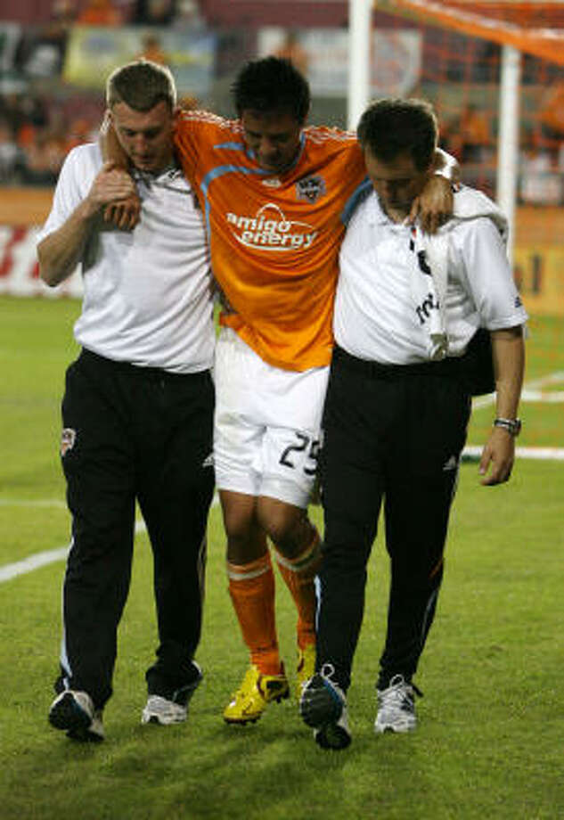 Dynamo forward Brian Ching gets some help leaving the field after straining his left hamstring. Photo: Billy Smith II, Chronicle