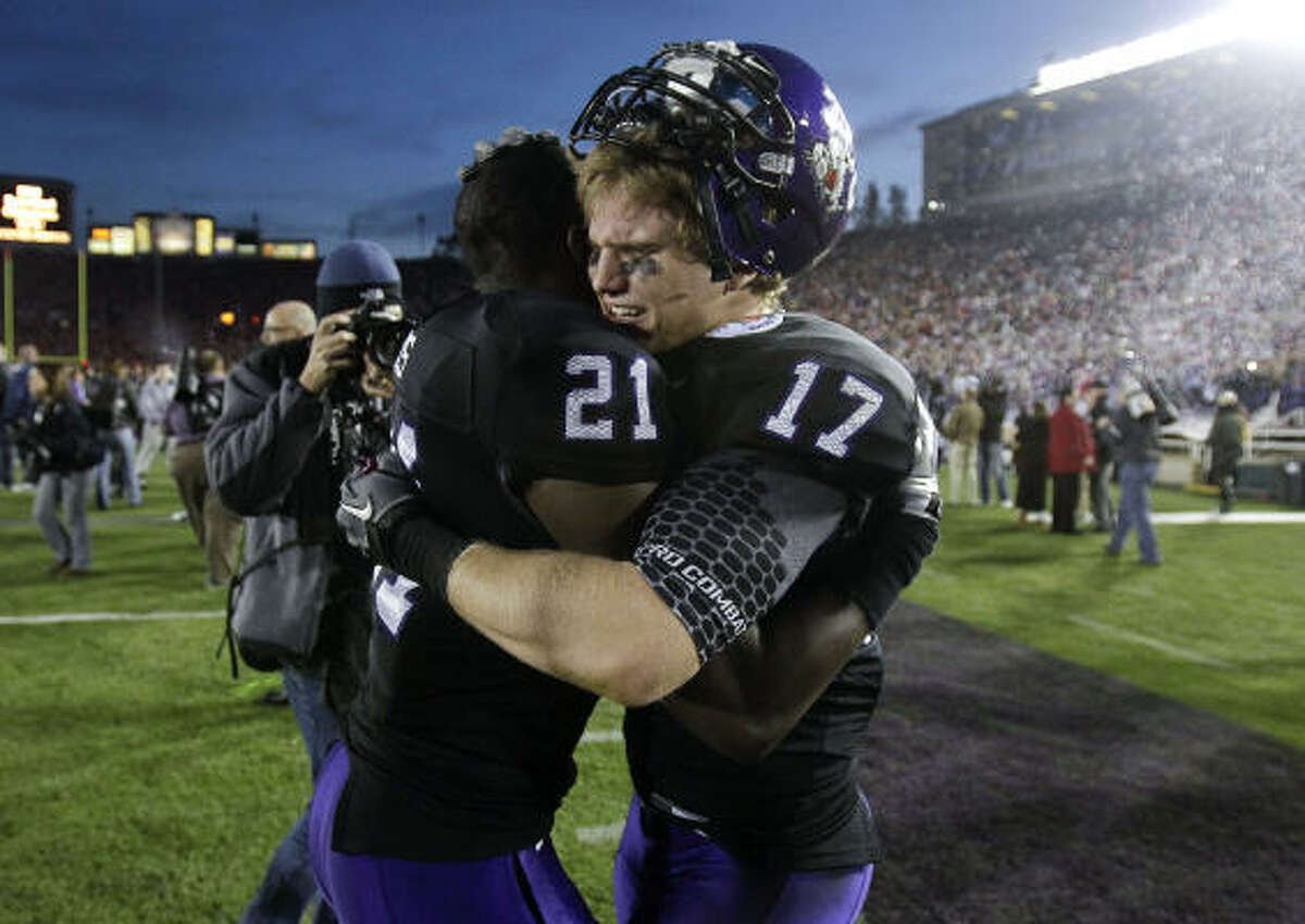 TCU safety Tyler Luttrell (17) hugs teammate Johnny Fobbs after their win over Wisconsin.