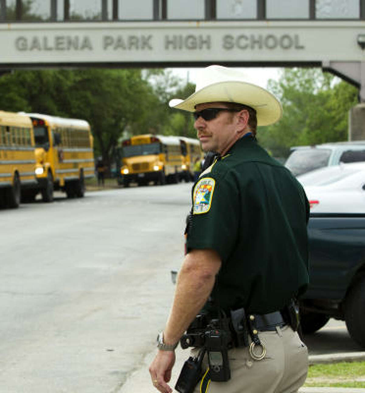Deputy Constable Mark McGinnis prepares to direct traffic outside Galena Park High School on Friday. He has been stationed at the school for 15 years.