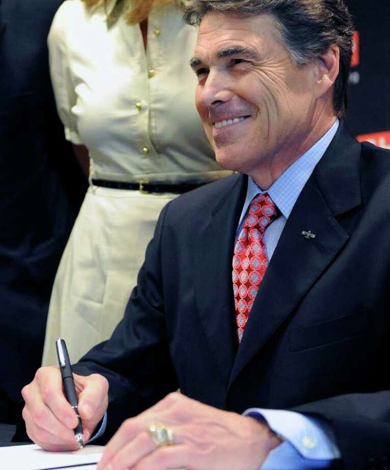 Texas Gov. Rick Perry smiles as he signs a ceremonial bill for a new tort reform measure Wednesday, July 27, 2011, in Houston. (AP Photo/Pat Sullivan) Photo: Pat Sullivan, STF / AP