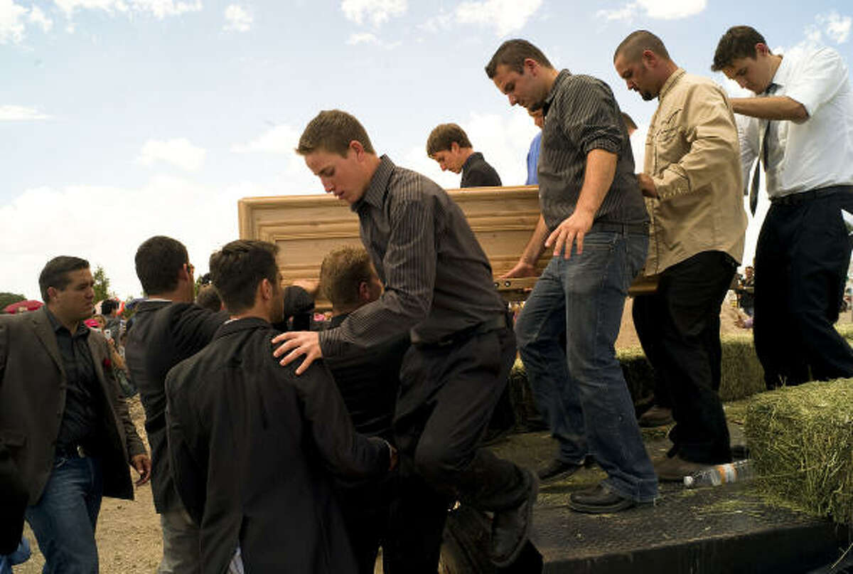 Benji LeBaron's brother Eric, center, and other relatives carry his casket to his grave Thursday.