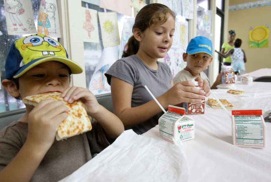 Michael Smith, 3, from left, his sister, Amy, 9, and brother Manuel, 7,  have lunch at the Oakwood Gardens Apartments. Photo: Melissa Phillip, Chronicle