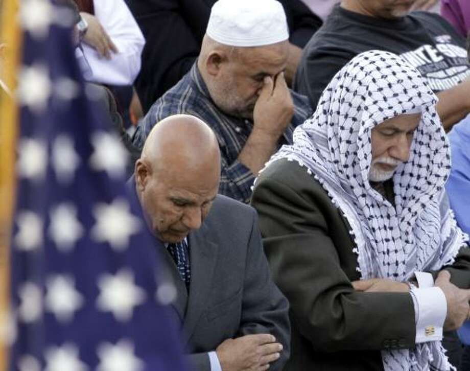 An American flag adorns the stage as worshippers gather for prayer during Eid al-Fitr morning services marking the end of the Muslim holy month of Ramadan in Bridgeview, Ill., on Friday. Photo: M. Spencer Green, Associated Press