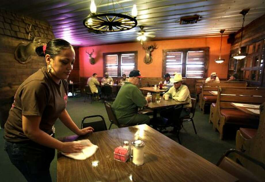 Veronica Aguirre clears a table at JJ's Country Store in Cotulla after the lunch rush. An increased number of oil field workers are in the area. Photo: Bob Owen :, San Antonio Express-News