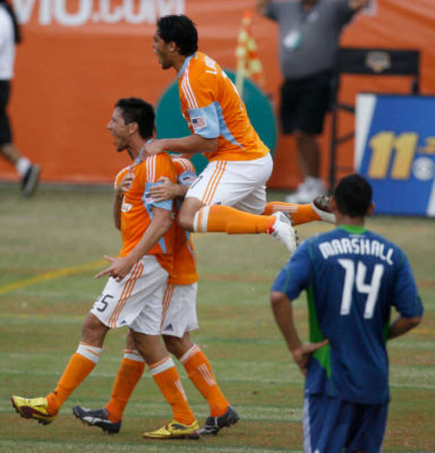 Houston Dynamo forward Brian Ching, left, celebrates his goal in the 96th minute. Photo: Julio Cortez, Chronicle