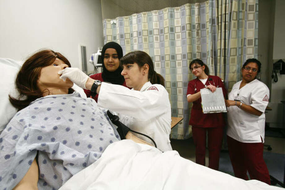 Aysha Rizwan, from left, Magdalena Deaton and other first-year nursing students attend to a mannequin at the Texas Woman's University simulation lab last week in Houston. The mock hospital ward allows students opportunities to practice and apply the skills they've learned.  Photo: Michael  Paulsen, Chronicle