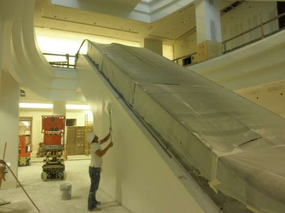 COURTESY OF FORT BEND COUNTY COMING TOGETHER: A worker paints an escalator in the justice center building.