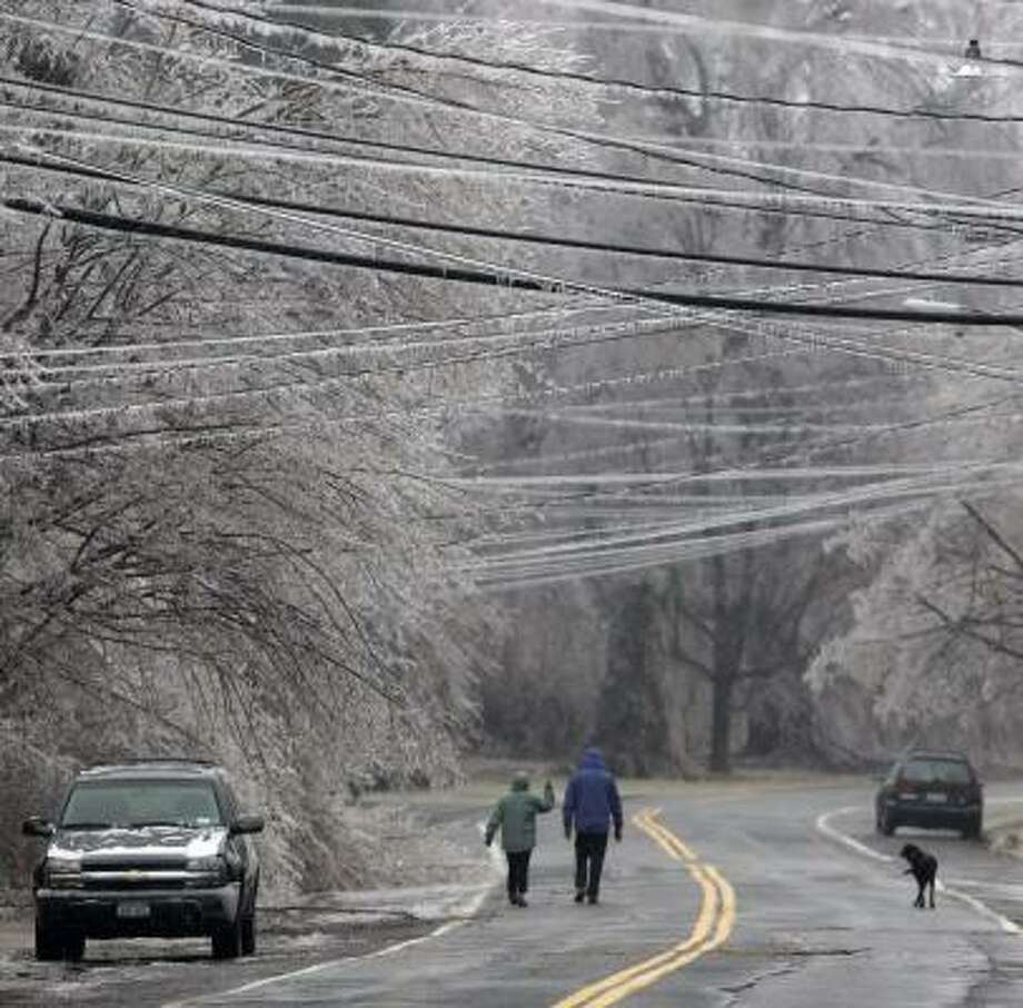 Pedestrians make their way down an ice-covered street Friday in Kinderhook, N.Y. Photo: MIKE GROLL, ASSOCIATED PRESS