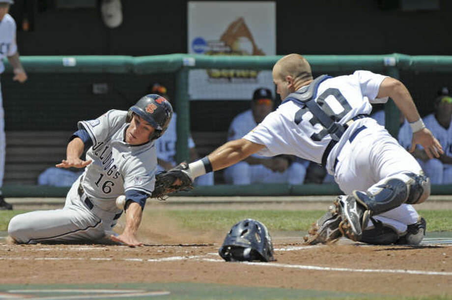 Fresno State's Danny Muno, left, scores at home plate as Rice's catcher Adam Zornes, right, loses the ball. Photo: Ted Kirk, AP