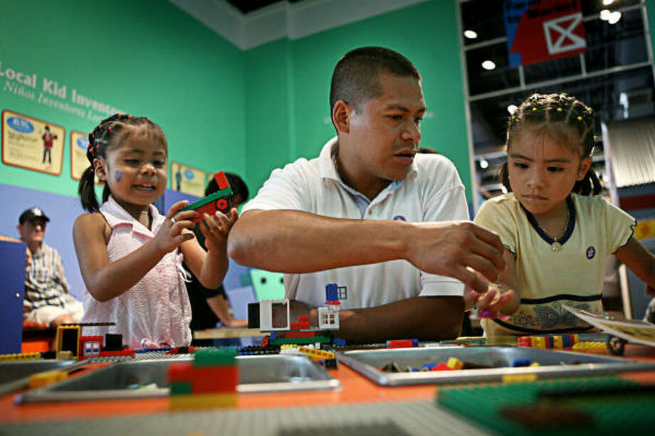 Carlos Rivera helps his daughters, Krystal, 4, left, and Karla, 5, right, build Lego structures at the Children's Museum's Invention Convention and Invention Workshop. Photo: ERIN TRIEB, FOR THE CHRONICLE