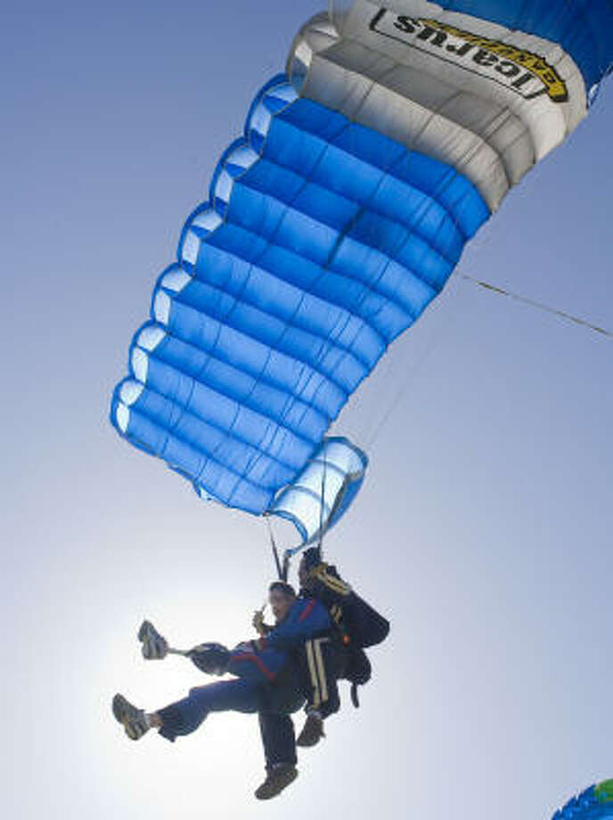 """U.S. Army Sgt. John Botts, left, completes a tandem skydive with instrutor Ben Morson during the """"Wounded Warriors Skydive with Airborne Amputees"""" in Rosharon on Sunday. Photo: James Nielsen, Chronicle"""