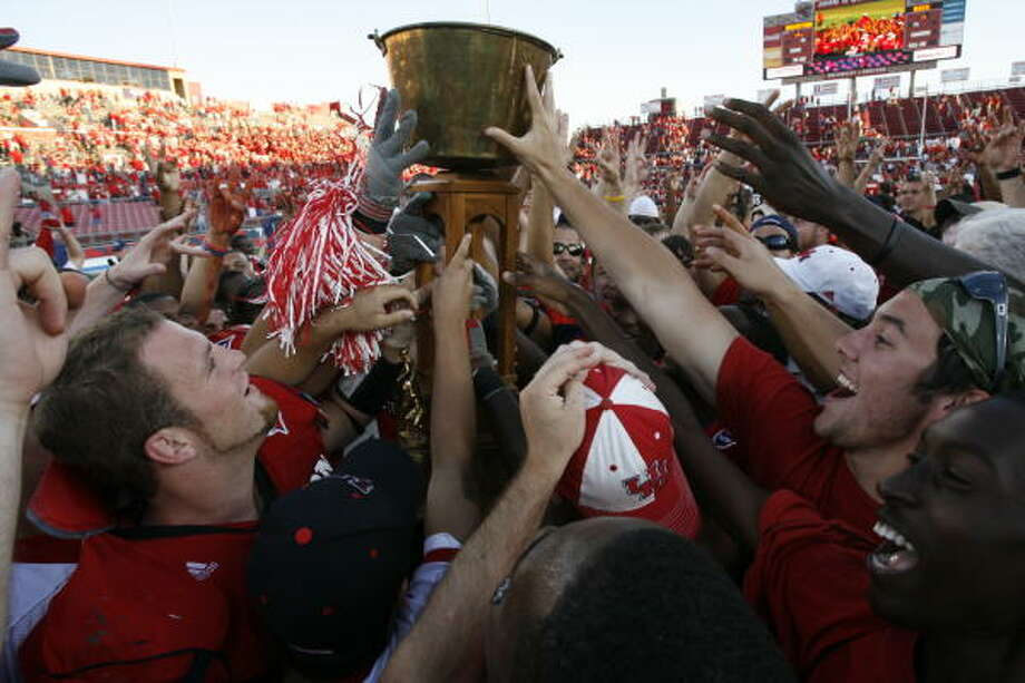 UH's Tate Stewart (lower left) helps hoist the Bayou Bucket after the Cougars' 56-48 win over Rice last year. Photo: Kevin Fujii, Houston Chronicle