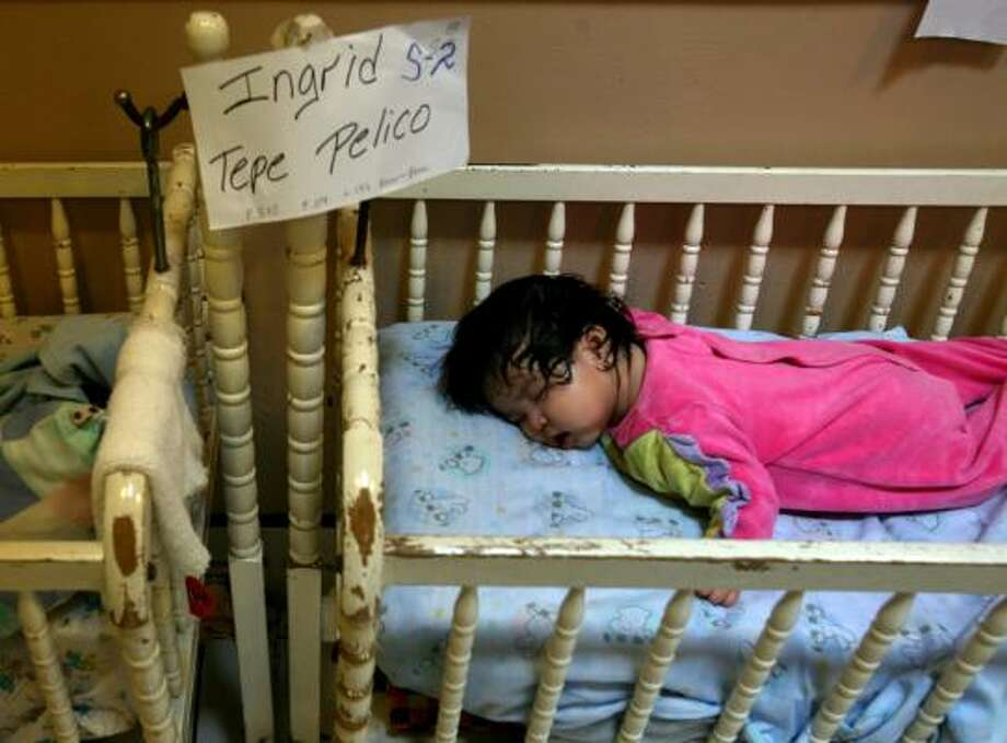 An infant girl sleeping at Casa Quivira in Antigua is one of dozens of children taken into protective custody as Guatemala authorities investigate whether the group home owners were either stealing youngsters or forcing parents to give them up for foreign adoptions. Photo: RODRIGO ABD, Ap
