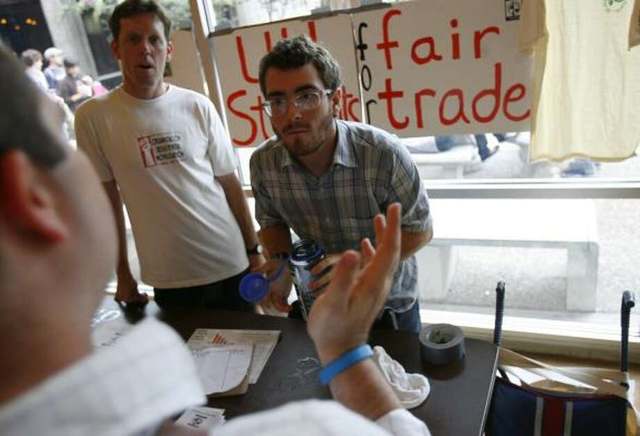 Tim O'Brien, left, and Ross Barnard discuss fair trade coffee with a University of Houston student. Photo: SHARÓN STEINMANN, CHRONICLE