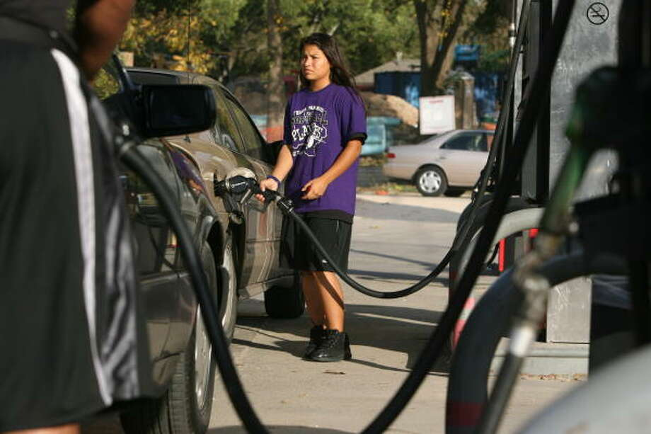 Robin Heredia, 16, pumps fuel for her mother Friday amid rising gasoline prices at a Houston station. Photo: Mayra Beltran, Chronicle