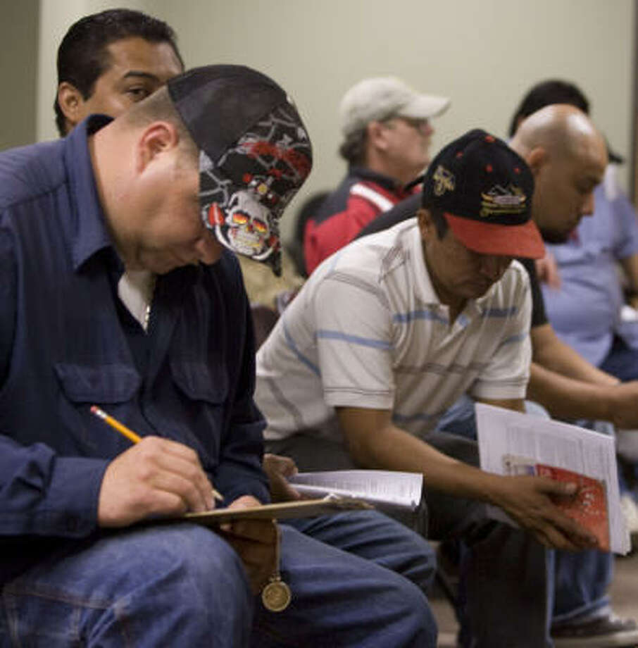 Workers fill out forms at the Port of Houston for the Transportation Worker Identification Credential program. Photo: Billy Smith II, Chronicle