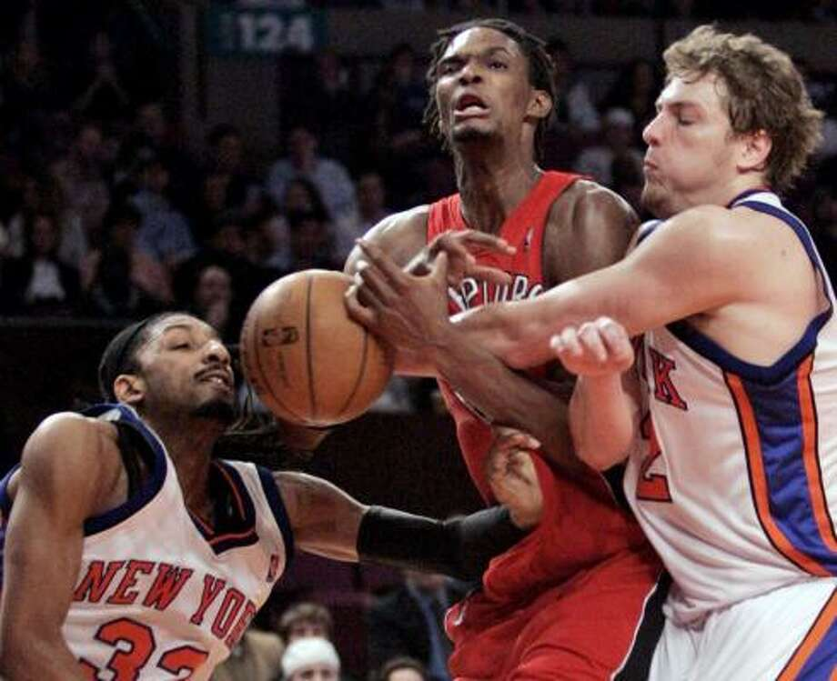 New York's David Lee, right, fouls Toronto's Chris Bosh, center, as Knicks teammate Renaldo Balkman tries to help Friday. Bosh scored 40 points in the Raptors' 99-90 victory. Photo: FRANK FRANKLIN II, ASSOCIATED PRESS