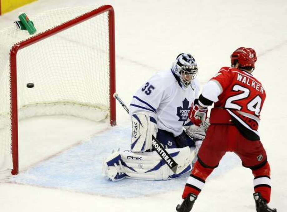 Camped just outside the crease, the Hurricanes' Scott Walker is in position to tip a shot past Maple Leafs goalie Vesa Toskala for the winning goal in overtime. Photo: JASON ARTHURS, MCCLATCHEY-TRIBUNE