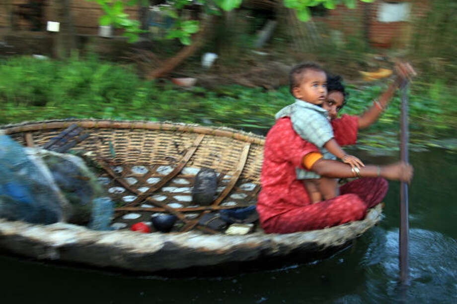 A mother and child travel on Kerala's backwaters. Some aspects of life remain unchanged for generations. Photo: Dai Huynh, CHRONICLE