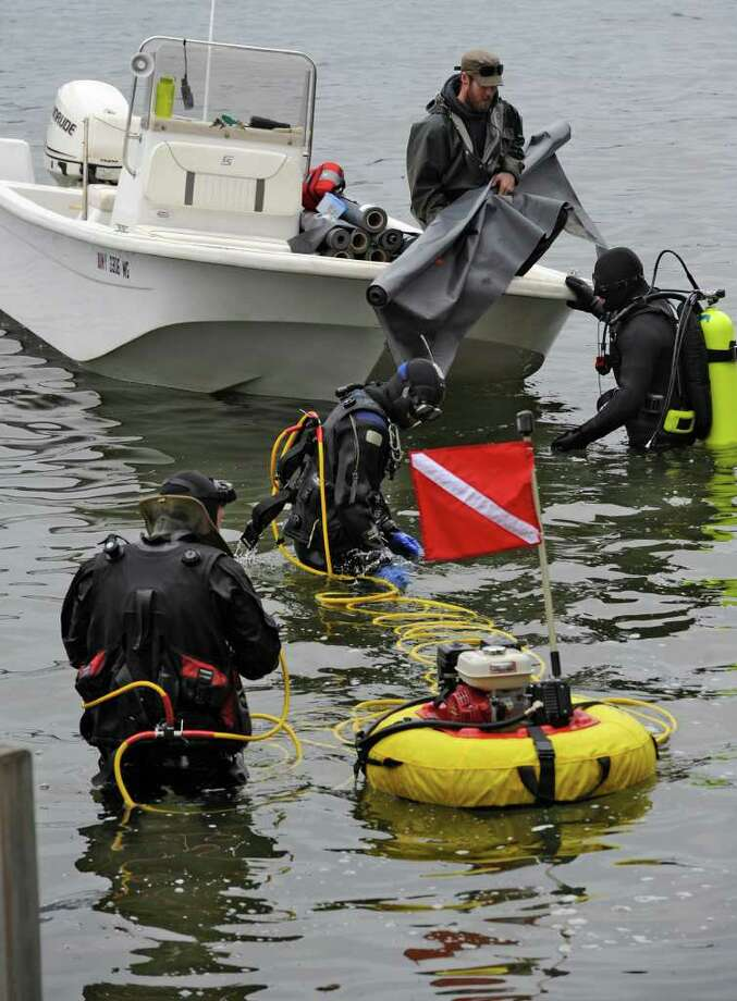 Divers and support members of Aquatic Invasive Management  of Lake Placid prepare to lay a mat on the lake floor to attempt to eliminate Asian Clams that have invaded Lake George, N.Y., in this April 25, 2011, image.   (Skip Dickstein / Times Union archive) Photo: SKIP DICKSTEIN / 00012910A