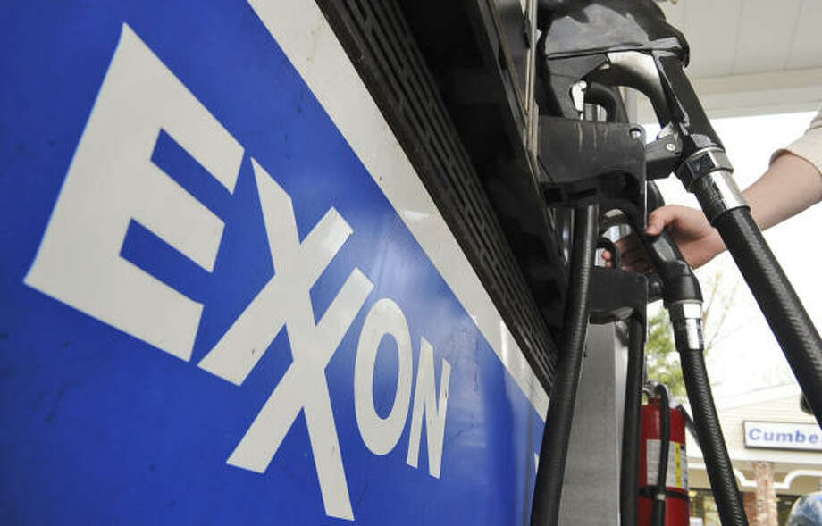 A customer pumps gasoline at a Middleton, Mass., Exxon station on Thursday. Exxon Mobil reported a $10.9 billion quarterly profit, a 17 percent increase, but the company's production shortfall dismayed investors. Photo: Lisa Poole, Associated Press