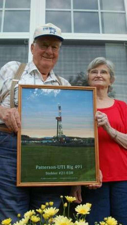 Oscar and Lorene Stohler hold up a picture of the oil rig built not long ago on their property. In less than a year they've become millionaires, and more wells are in the works. Photo: JAMES MACPHERSON, ASSOCIATED PRESS