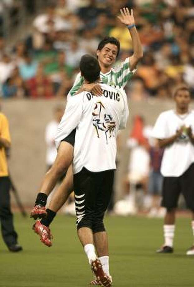 Goalkeeper Vojislav Dragovic lifts up Gabriele Cirigliano, 17, from Italy, who won a local competition to compete during the Free Kick Masters competition Saturday in Houston. Photo: Bob Levey, AP