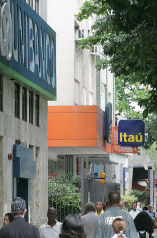 Pedestrians pass by Unibanco and Itaú branches Monday in Rio de Janeiro. The banks' plan to merge must still be approved by Brazil's central bank Photo: Ricardo Moraes, Associated Press