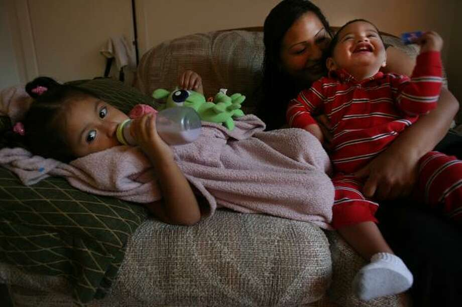 Veronica Peña plays with Leo, 1, and Leila, 2, in her northwest Houston apartment. She is raising three other sons as well, without child support from any of the three men who fathered her children. Photo: MAYRA BELTRÁN, CHRONICLE