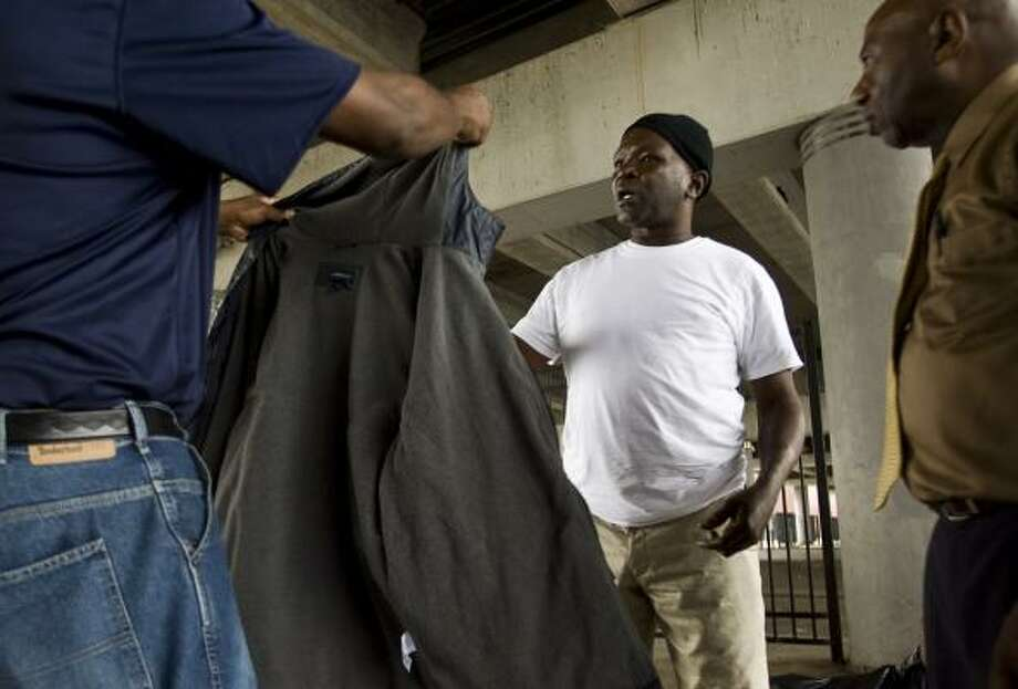 Star of Hope Mission volunteer Johnnie Wiggins, left, and outreach coordinator Lee Morgan give a coat to John Goss on Tuesday anticipating very cold weather the next few days. Photo: MICHAEL PAULSEN, CHRONICLE