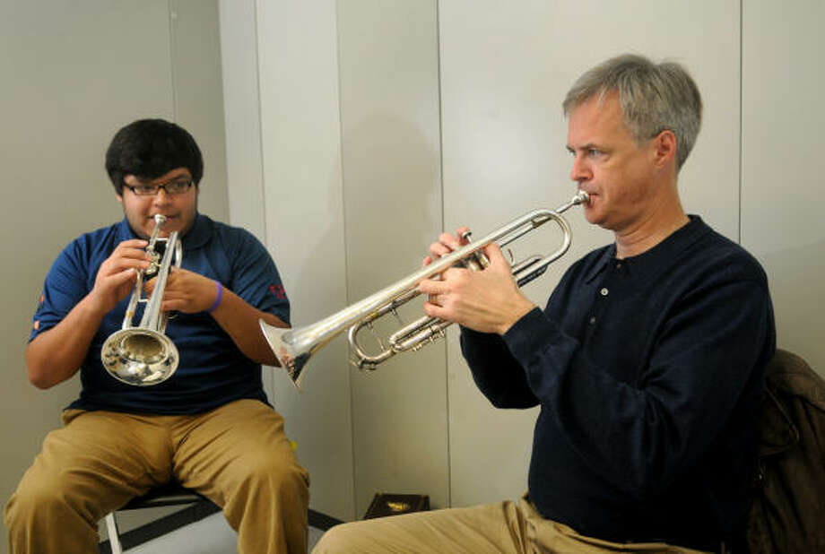 DUET: Tom Tillotson, right, of Kingwood, plays with Lone Star College-North Harris student Alex Villanuevea, 22, during a music lesson at the college last week. Tillotson is a member of the Paragon Brass Ensemble that will be performing in Revels Houston starting this weekend at the Lowe Theater in the Virginia Stuller Tatham Fine Arts Center. Tillotson began playing the trumpet when he was 11 years old and graduated from Rice University with a degree in trumpet performance. Photo: Jerry Baker, FOR THE CHRONICLE