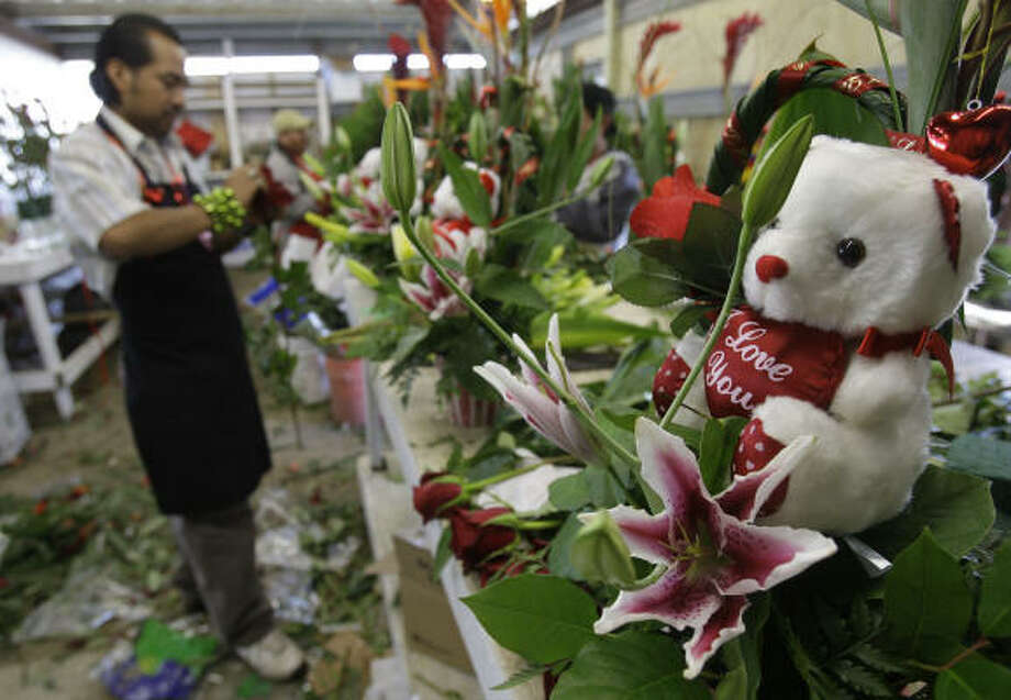 Valentine's Day sales may be down nationally, but that doesn't deter Martin Sanchez from creating flower arrangements at Fannin Flowers, at 4803 Fannin. Photo: Melissa Phillip :, Chronicle
