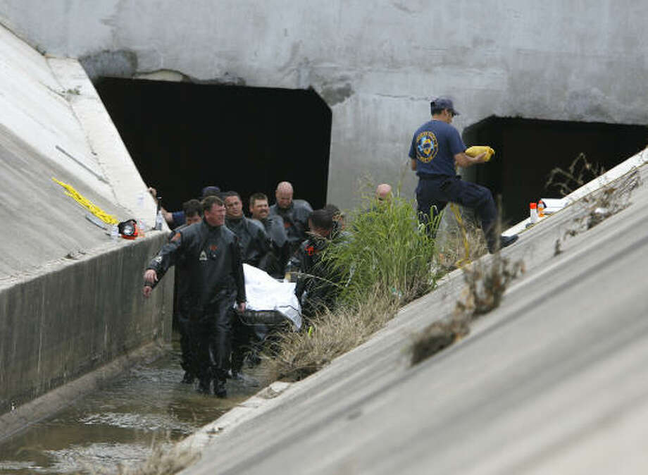 A dive crew Wednesday retrieves the body of a motorist from a culvert alongside the Interstate 10 frontage road near Beltway 8. Apolonio Fuentes, 43, of Pasadena, was driving a Toyota RAV4 when it was swept away by Tuesday's floodwaters. Photo: Karen Warren, Chronicle