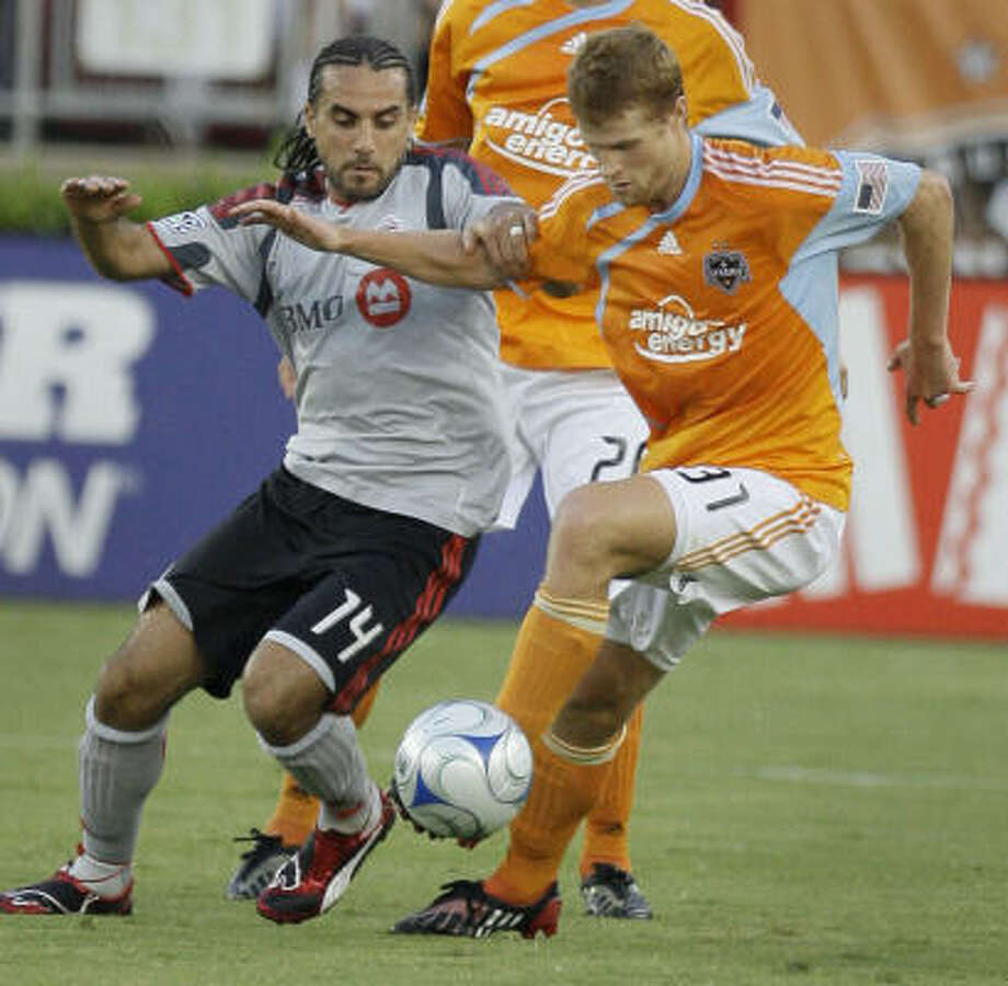 Toronto FC (14) Dwayne DeRosario , left, and Houston Dynamo (31) Andrew Hainault, right,  battle for the ball. Photo: Melissa Phillip, Chronicle