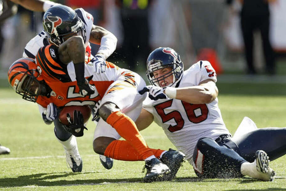 With help from Glover Quin, top, Texans linebacker Brian Cushing puts the clamps on Bengals receiver Chad Ochocinco in the second half Sunday. Cushing forced two fumbles and had the game-saving interception in the win. Photo: Brett Coomer, Chronicle