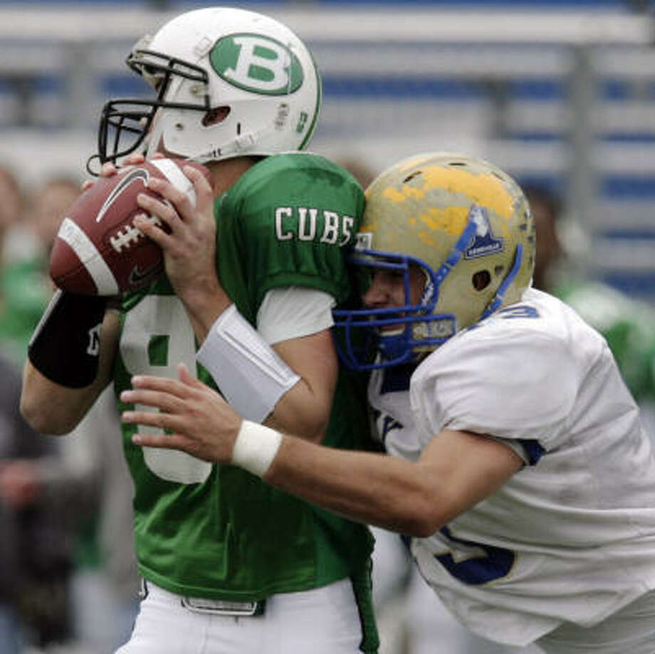 Brenham quarterback Ty Schlottmann, right, has taken plenty of big hits like this one last week against Kerrville Tivy, but he has rebounded to lead his team to the state finals. Photo: KIN MAN HUI, San Antonio Express-News
