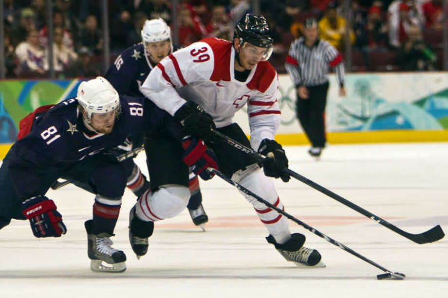 American forward Phil Kessel knocks the puck away from Switzerland's Raffaele Sannitz. Photo: Smiley N. Pool, Chronicle Olympic Bureau