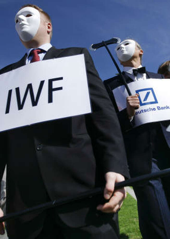 Masked activists of the anti-globalization movement Attac protest in front of a chancellery in Berlin on the Greece debt crisis. Photo: Markus Schreiber, AP