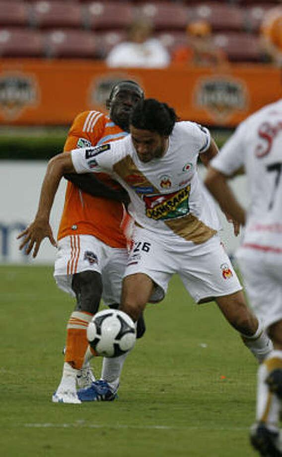 Dynamo midfielder Dominic Odura fights Morelia's Mauricio Romero for the ball. Photo: Mayra Beltran, Chronicle