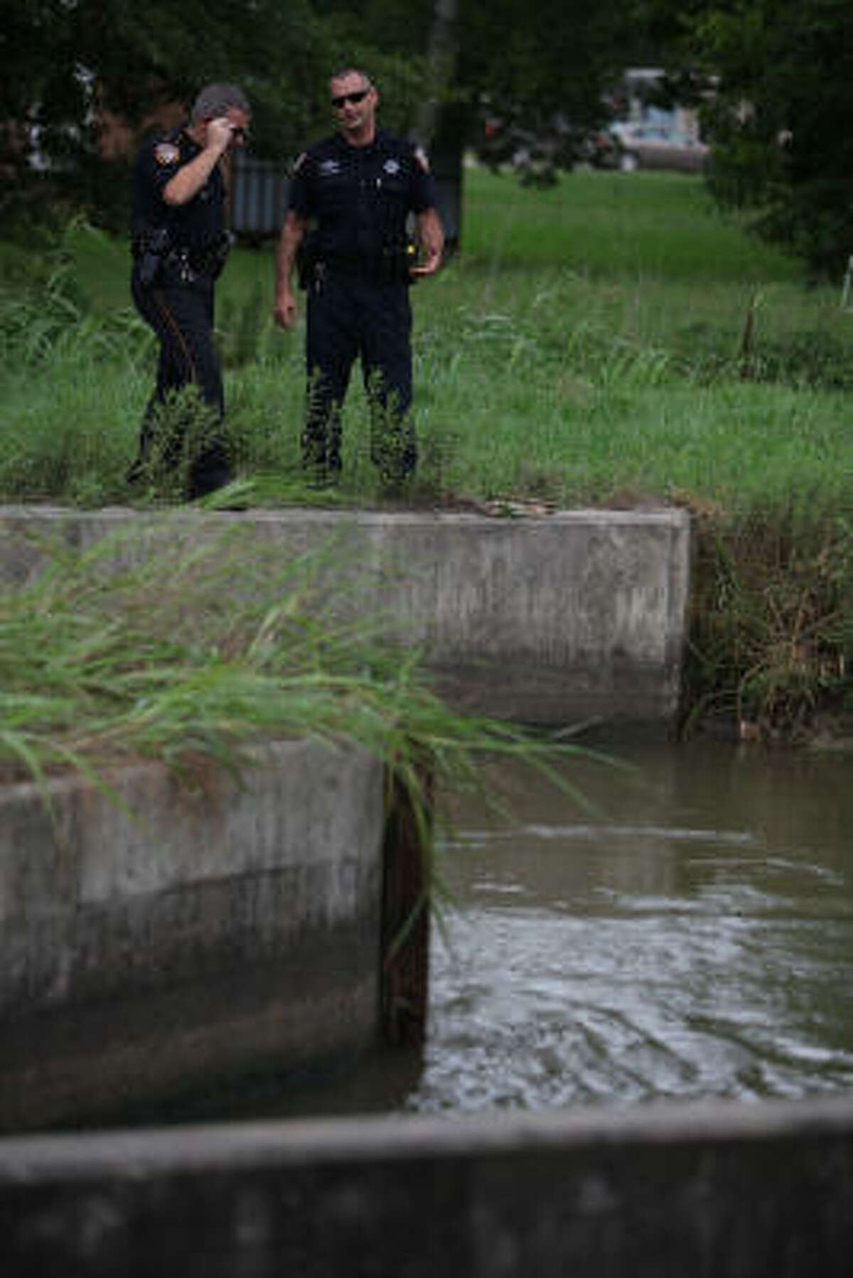 Deputies stand along the canal where a colleague drowned near his home in Baytown.