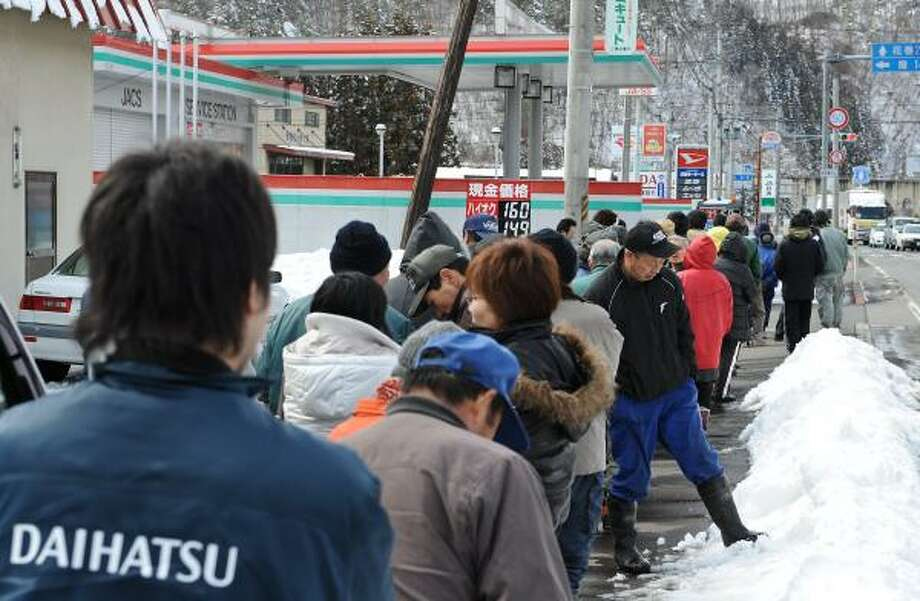 In the town of Tonoi, people wait in front of a closed gas station after an earthquake and tsunami hit the Japanese coast. Once they get a number, they can return later for fuel. Photo: NICHOLAS KAMM, AFP/Getty Images