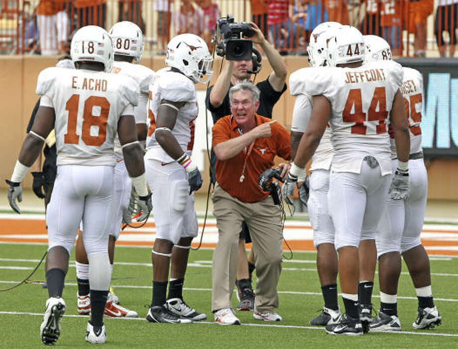 Texas coach Mack Brown, center, is fired up as he issues instructions to his players during Sunday's spring game. Photo: Michael Thomas, AP