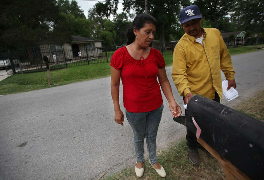 Eleuteria and Santiago Flores pick up mail at a property they own across the street from the house they purchased for $10,000, received a deed for and spent $30,000 fixing up only to find out they never owned the property and had been victims of a scam. Photo: Mayra Beltran, Chronicle
