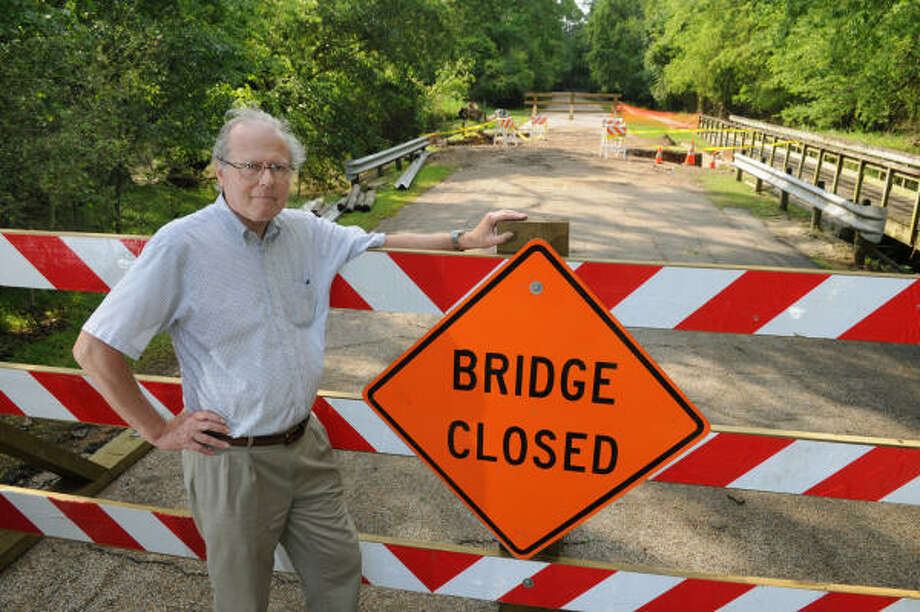 PARK CLOSED TOO: Dick McGucken, Chairman of the Kingwood Service Association Parks Committee, stands in front of the bridge at the entrance to River Grove Park where an 6-foot deep sinkhole formed to block the park?s only access road. Photo: Jerry Baker, For The Chronicle