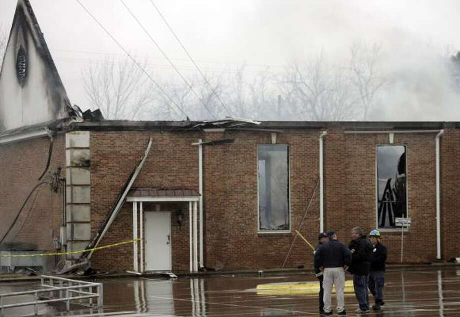 Investigators talk beside the burned Russell Memorial United Methodist Church in Wills Point on Feb. 4. The seventh church fire set this year in East Texas by arsonists destroyed the house of worship. Photo: Mike Fuentes, Associated Press