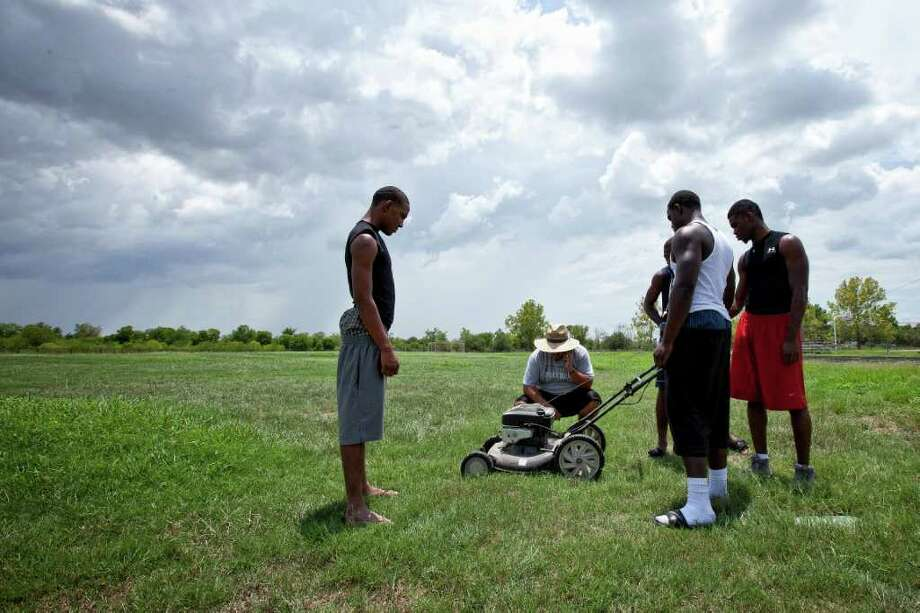 "Sterling High School head football coach, Eddie Chinea, works to struggles to start a lawnmower as players, from left, Jacobe Robertson, Joryus Batiste, Jaquan McKnight and Adian Robeson, look on, Wednesday, July 27, 2011 around on the practice football field at Sterling High School in Houston, Texas. After multiple requests to HISD for field watering and maintenance, Chinea, with his own personal mower, and a few of his top players, took the job into their own hands. ""We start practice on Monday, and no one else is going to do it,"" remarked Chinea, referring to the field conditions. (Todd Spoth for the Chronicle) Photo: TODD SPOTH, Photographer / Todd Spoth"